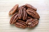 stock photo of pecan  - a group of pecan halves on wooden flat - JPG