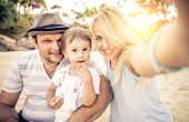 pic of young baby  - Mom and dad playing with their handsome son - Family and baby outdoors - Young beautiful mother taking a self portrait with her family ** Note: Shallow depth of field - JPG