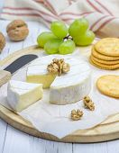 stock photo of brie cheese  - Soft brie cheese with sweet grapes nuts and crackers - JPG