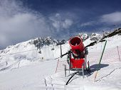stock photo of cannon  - Modern red snow cannon near the ski piste in the high mountains - JPG