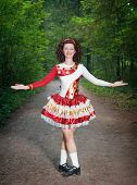 stock photo of wig  - Young woman in irish dance dress and wig welcoming outdoor - JPG