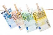 image of pegging  - Euro banknotes hanging with peg from a rope isolated on white background - JPG