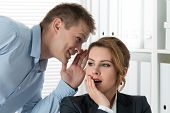 stock photo of waste management  - Young man telling gossips to his woman colleague at the office - JPG