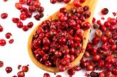 stock photo of peppercorns  - red peppercorns in wooden spoon isolated on white - JPG