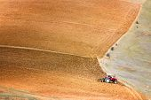 stock photo of plowed field  - Tractor plowing a large field near Concepcion Peru
