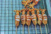 picture of squid  - Fresh fried squid on a stick at the Market in Krabi Town Thailand - JPG