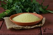 stock photo of cereal bowl  - cous cous cereal in a clay bowl on wooden table - JPG