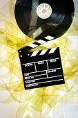 picture of mm  - Movie clapper on 35 mm cinema reel unrolled yellow filmstrip on white background vertical - JPG