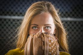 picture of softball  - Dramatic Young Woman with Softball Glove Covering Her Face Outdoors - JPG