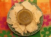 pic of mexican food  - Serving of tortilla chips with bowl of salsa verde on colorful place mat typical Mexican Restaurant Appetizer - JPG