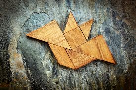 foto of tangram  - abstract picture of a flying bat built from seven tangram wooden pieces over a slate rock background - JPG