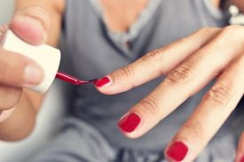 image of swagger  - closeup of a young woman applying red nail polish to her fingernails - JPG