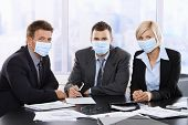 stock photo of swine flu  - Business people fearing h1n1 swine flu virus wearing protective face mask during meeting at office - JPG