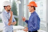 Постер, плакат: Cheerful two engineers are discussing the building