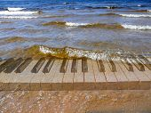 picture of chopin  - classic piano keyboard under transparent surf waves - JPG