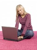 Young Blonde Woman Sitting On The Pink Carpet With Laptop