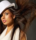 Attractive lady in white hat and blowing hair