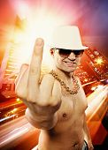 image of gangster necklace  - Man showing middle finger in front of night city - JPG
