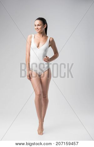 poster of Beauty concept. Full length portrait of happy fit young woman posing in white swimsuit. She is standing with arm akimbo and smiling. Isolated