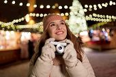 holidays, photography and people concept - beautiful happy young woman with camera at christmas mark poster