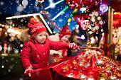 Kids At Christmas Fair. Children Shopping Xmas Gifts. poster