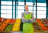 picture of grocery store  - A grocery store owner standing in front of vegetables and fruit - JPG