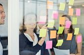 Professional business people discussing ideas presented on colored sticky notes. Businesswoman showi poster