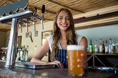 Portrait of happy young barmaid holding beer glass at restaurant poster
