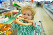 Shopping Food Store, Cute Boy Sitting In Shopping Cart In Supermarket On Family Shopping. Grocery St poster
