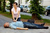 stock photo of cpr  - Woman makes first aid for a man with heart attack in the street - JPG