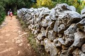 Stone Rock Fence Wall Gabion And Family Hiking In Background. poster