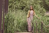 Beautiful Hippie Girl Standing On A Wooden Bridge In The Park poster