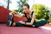 Photo of energetic young woman 20s wearing tracksuit stretching her legs during workout on sports gr poster
