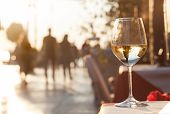 Glass Of Chilled White Wine Over Sunset City Background poster