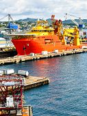 A Large Orange And Yellow Colored Offshore Construction Vessel (ocv) Is In A Dry Dock Of A Shipyard  poster