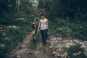 Homeless Father And Daughter Walk Through The Garbage Dump. The Concept Of Environmental Pollution,  poster
