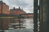 Low Angle View Of Channel And Historic Warehouses In The Speicherstadt District Of Hamburg Against C poster