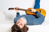 Happy Young Man Lying Back On Sofa With Guitar. Smiling Guitarist Relaxing On White Sofa. Close-up C poster