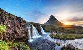Famous Kirkjufell mountain with cascade waterfalls, Iceland. Kirkjufell is one of the most beautiful poster