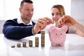 Couple Inserting Coin In Piggybank Near Increasing Profit Over Desk poster