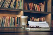 Eyeglasses Lying On Book And Coffee Drink In Library Room With Copy Space For Text Against Bookshelf poster