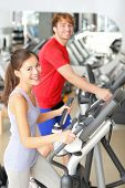Gym people in fitness center doing walking workout on moonwalker fitness machines. Young couple, asi