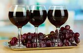 Red wine in glass on salver on room background