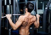 stock photo of half naked  - Athletic young man works out on training apparatus in fitness gym - JPG