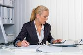 stock photo of statements  - an accountant at work in the office with calculator - JPG