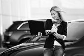 Young businesswoman using laptop on the car parking