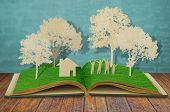 image of cutting trees  - Paper cut of family symbol on old grass book  - JPG