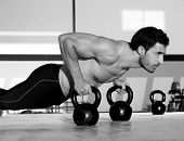 Turnhalle Mann Push-up Stärke Pushup Training mit Kettlebell in einem Training