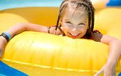 image of one piece swimsuit  - Little girl  sitting on inflatable yellow ring in swimming pool - JPG