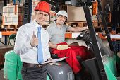 foto of forklift driver  - Portrait of supervisor gesturing thumbs up with forklift driver sitting behind - JPG